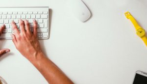 Hands typing on a keyboard to demonstrate someone starting a blog on WordPress.