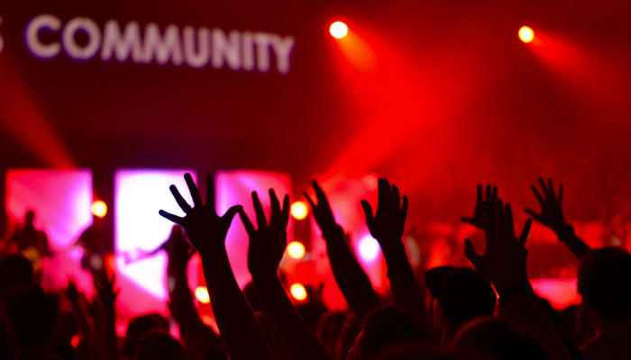 A crowd of people and the word community. Image: Unsplash.com.