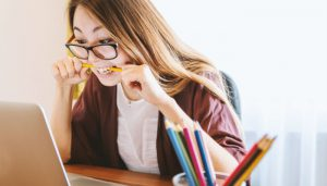 A woman biting a pencil wondering if Wealthy Affiliate is worth the money or a scam?