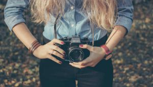 A photo of a woman holding a camera from the free stock photo site Unsplash.