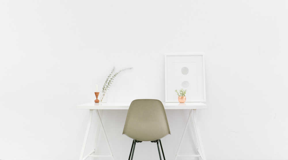 A photo of a desk and chair in a white room from free stock photo site Stocksnap.io.