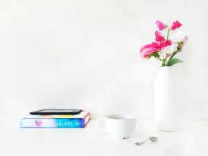 A free feminine stock photo of a desktop, with a book, kindle, cup and flowers, by Creative Convex.