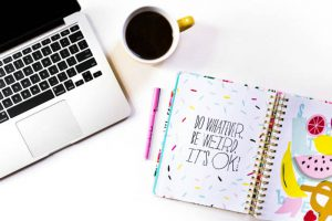 A free feminine, girly styled stock photo of a desktop, with a diary, cup and pink pencil, by Wonderlass.