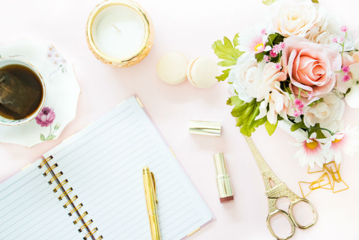 A free feminine styled stock image of a pink desktop and stationery items from She Bold.