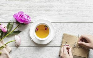 A feminine styled free stock photo of a desktop with tea cup and vintage parcel from Rawpixel.com.